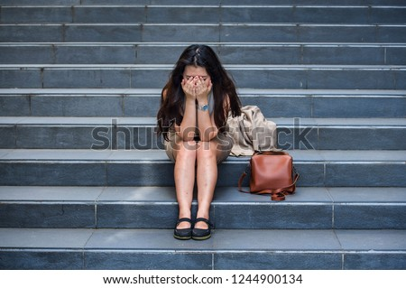 young depressed and desperate Asian Korean businesswoman crying alone sitting on street staircase suffering stress and depression crisis being victim of mobbing or fired losing her job #1244900134