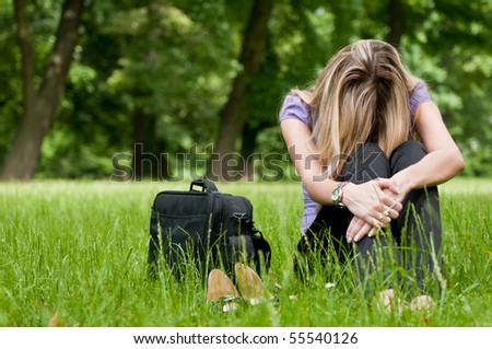 Young depressed business woman siting in grass - notebook bag and shoes lying next