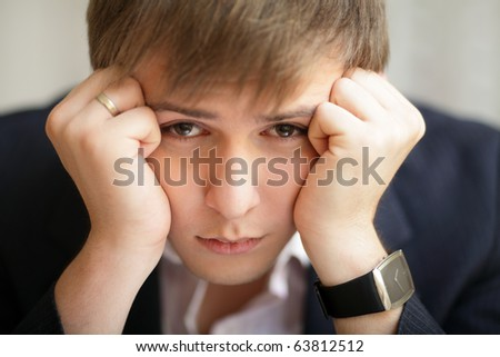 Young depressed businessman looking at the camera