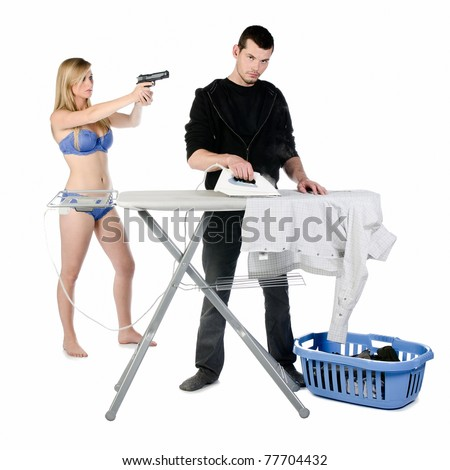 Young depressed man ironing his shirt while he's being threatened by his wife with a gun, studio shot fully isolated.