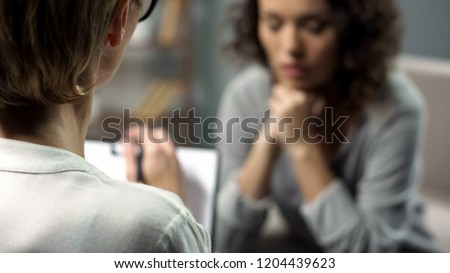 Young depressed woman talking to lady psychologist during session, mental health