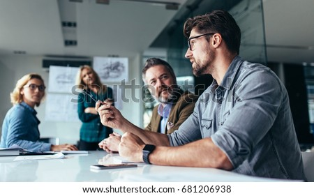 Young designer giving some new ideas about project to his partners in conference room. Business people discussing over new business project in office. Stockfoto ©