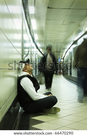 young despered guy sitting in subway tunnel