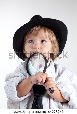 Young detective with magnifying glass, studio shot