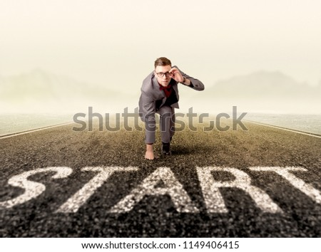 Young determined businessman kneeling at a start line  #1149406415