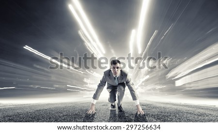 Young determined businessman standing in start position #297256634