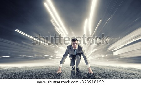 Young determined businessman standing in start position #323918159