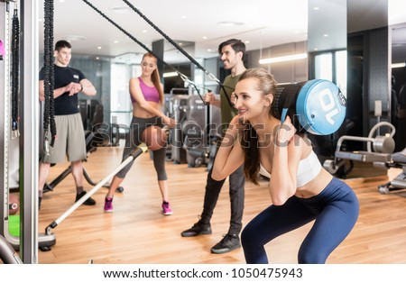 Young determined fit woman doing squats exercise, while holding on the back of her neck a heavy sandbag during group circuit functional training at the gym #1050475943