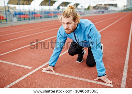 Young determined man in sportswear standing by start line on race track #1048683065