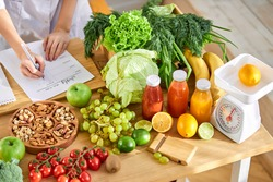 Young Dietitian writing diet plan, view from above on table with different healthy products