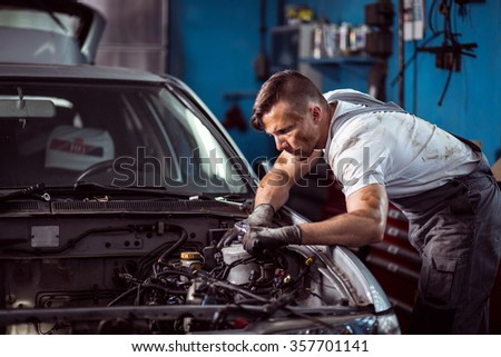 Young dirty mechanic working in car repair shop