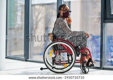Young disabled African American woman in wheelchair at home, wear face mask. Foto stock ©