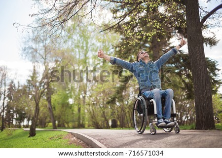 young disabled man in wheelchair walking park #716571034