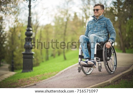 young disabled man in wheelchair walking park #716571097