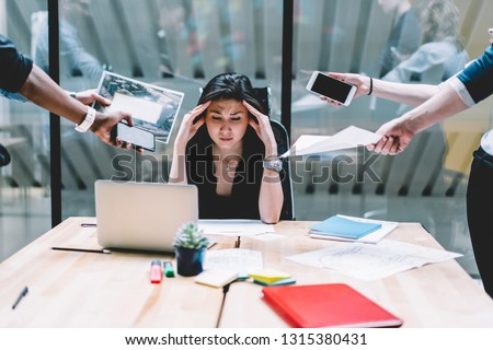 Young disappointed woman feeling headache from deadline surrounded by colleagues at workplace, multi-purpose female employee,tired of work and exhausted, stress in office. Overworked female in confuse Stock photo ©