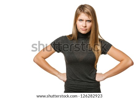 Young discontent teenager girl with hands on the hip, over white background
