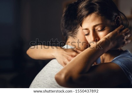Young distraught woman with eyes closed being embraced by her boyfriend.
