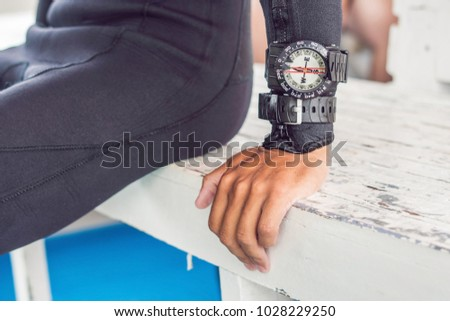 Young diver preparing an underwater compass for diving. #1028229250