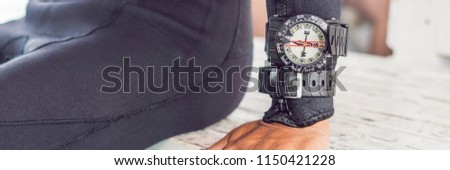 Young diver preparing an underwater compass for diving BANNER, long format #1150421228