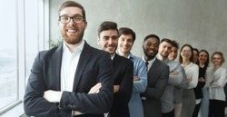 Young diverse business team posing with crossed arms, businesspeople headed with boss