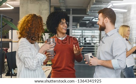 Young diverse colleagues sharing ideas and smiling during coffee break in office, panorama #1364341925
