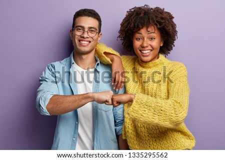 Young diverse couple give fist bump, agree to bring plan to life, smile broadly, have mixed race relationships, have good friendly partners, isolated over purple wall. I agree with you concept