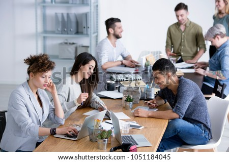 Young, diverse female and male coworkers brainstorming ideas for a project by a table at a start-up office