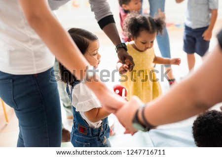 Young diverse kids standing with their parents