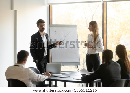 Young diverse man and woman coach stand talking making flip chart presentation for multiethnic employees, confident presenters advisors present strategy on whiteboard at team office training