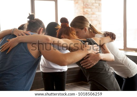 Young diverse people embracing uniting in circle standing together indoors, multiracial team of black and white friends hugging promising help support in common goal achievement, group unity concept