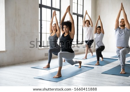 Young diverse people with African ethnicity yoga instructor standing on mats performing Warrior one asana or Virabhadrasana 1 pose. Work out physical activity in modern studio class, wellness concept