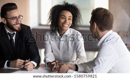 Young diverse professionals sit at boardroom desk working together on new profitable project african european arabian friendly partners solve issues having good mood, successful entrepreneurs concept
