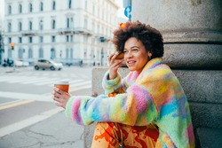 Young diverse unconventional multiethnic woman sitting outdoor drinking coffe-to-go and listening vocal instant message
