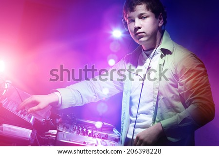 Young DJ playing records at a party in a nightclub.