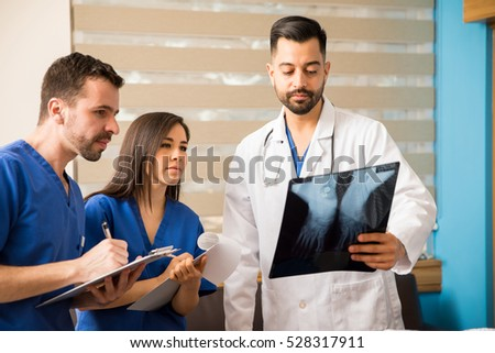 Young doctor and medical residents analyzing x-rays of a patient in a hospital room #528317911