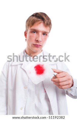 Young doctor holding bloody gauze pad with pair of scissors.