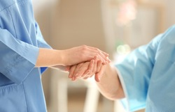 Young doctor holding hand of elderly woman on light background, closeup