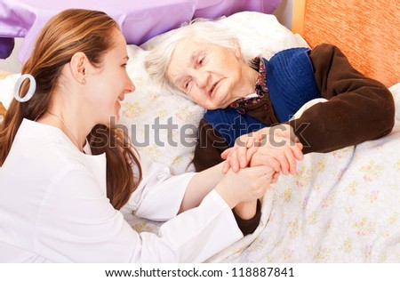 Young doctor holds the old woman\'s hands