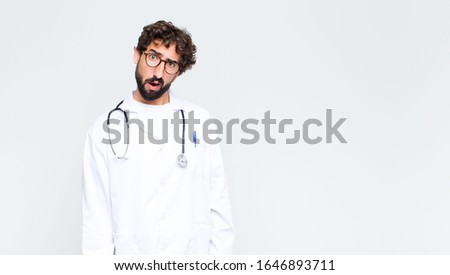 young doctor man feeling puzzled and confused, with a dumb, stunned expression looking at something unexpected against copy space wall