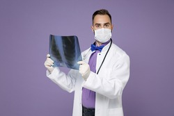 Young doctor man in medical gown face mask safe from coronavirus virus covid-19 hold X-ray of lungs fluorography roentgen isolated on violet background. Healthcare personnel health medicine concept