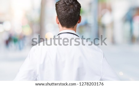Young doctor man wearing hospital coat over isolated background standing backwards looking away with arms on body