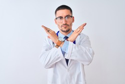 Young doctor man wearing stethoscope over isolated background Rejection expression crossing arms doing negative sign, angry face