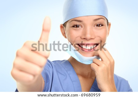 Young doctor or nurse giving thumbs up taking off the surgeon mask smiling. Asian / Caucasian female model in her mid 20s. - stock photo