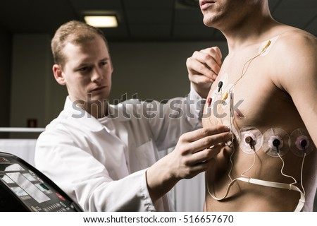Young doctor putting the cardiogram electrodes on patient's body