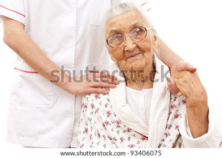 young doctor's hand on an old woman patient's shoulder