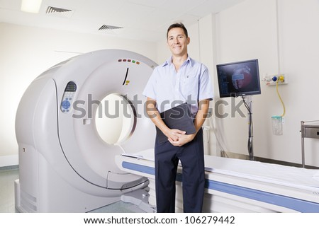 Young doctor standing in front of an MRI scanner