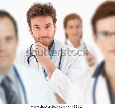 Young doctor standing in middle of medical team, looking at camera.?