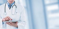 Young doctor using digital tablet against dental equipment