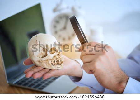 Young Doctor with a magnifying glass And watching the human skull on the hand. The medical student about the medical