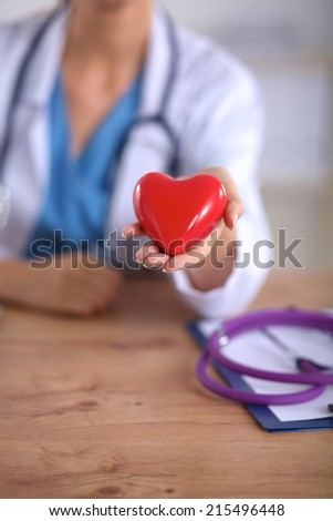 Young doctor with red heart symbol sitting at desk isolated #215496448